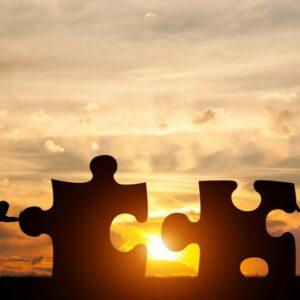 Two men connect two puzzle pieces. Sunset sky. Concept of busine